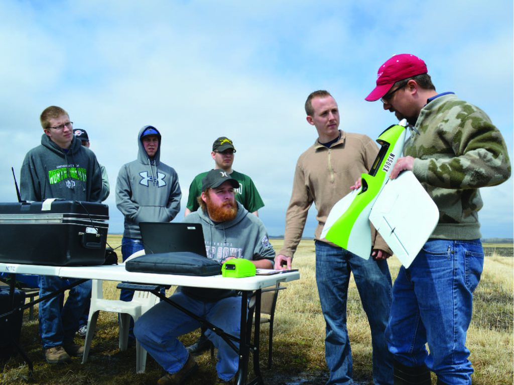 Instructor teaching students with drones in the field
