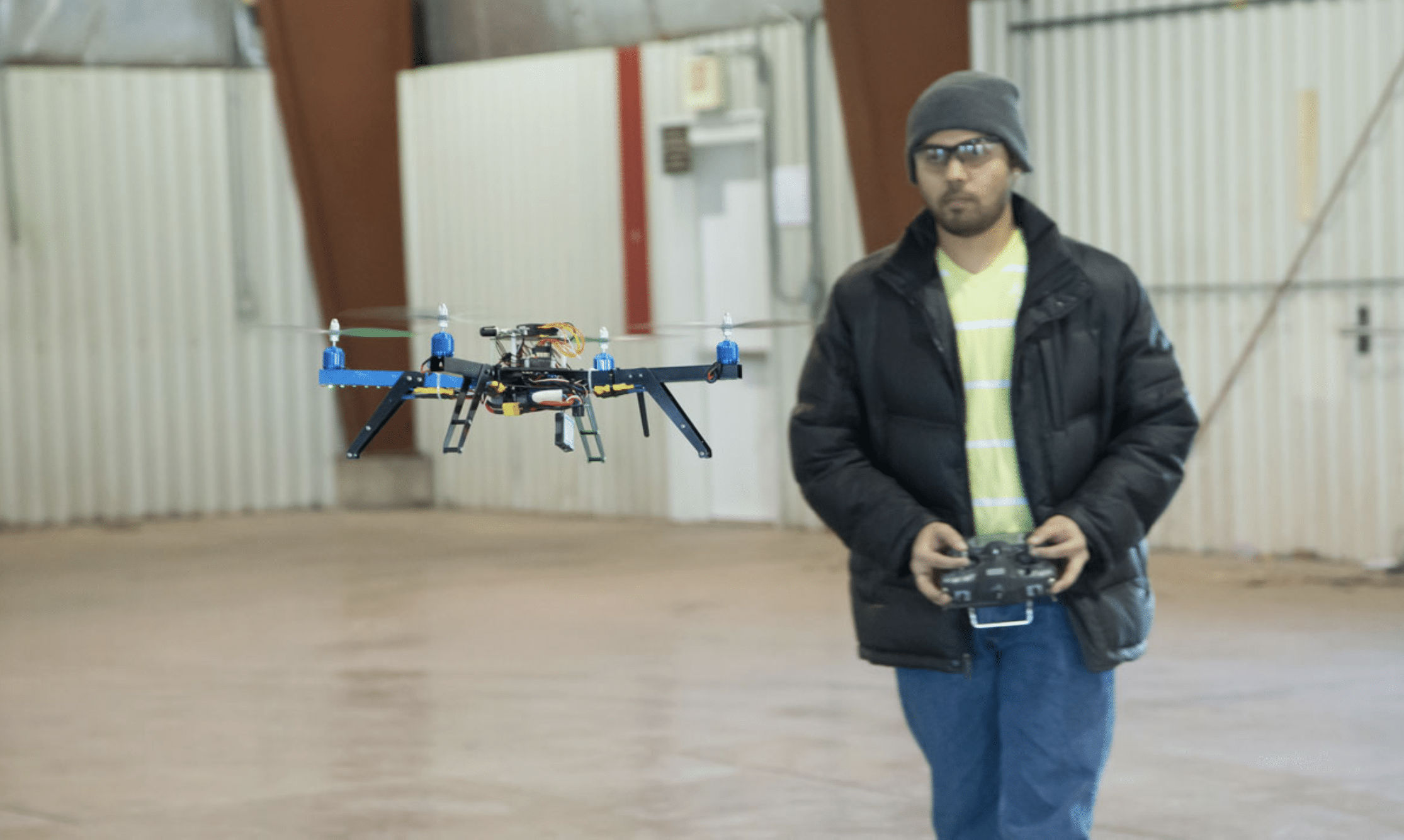 Man flying drone in building