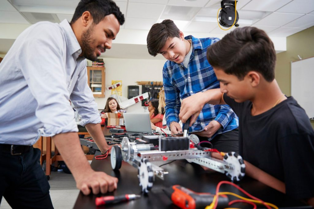 Teacher assisting students with robot