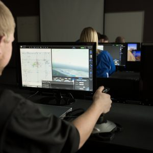 Dark image of students flying drone simulators