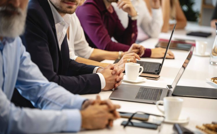 Businesspeople Seated Side by Side at Conference Table
